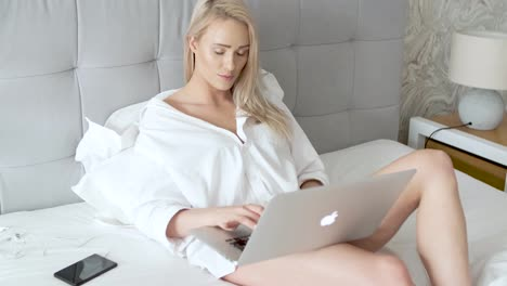 Beatutiful-woman-in-mens-elegant-white-shirt-sitting-in-bed-with-laptop