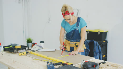 Woman-drawing-line-on-plywood-in-workshop-