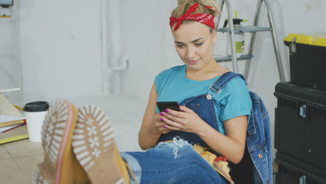 Smiling-woman-using-smartphone-sitting-at-workbench-