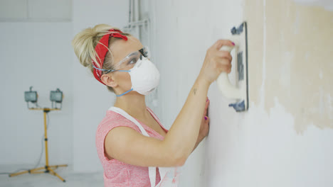 Woman-grinding-wall-with-sandpaper-