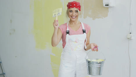 Delighted-woman-with-brush-and-paint-bucket-