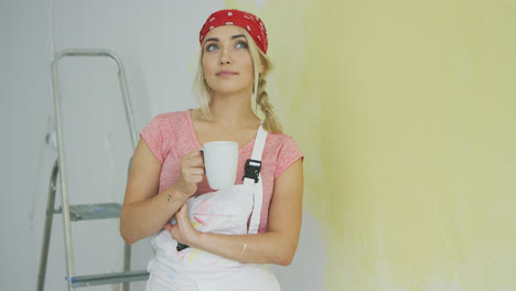 Female-painter-in-overalls-resting-with-drink-