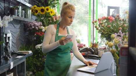 Worker-in-floral-shop-using-gadgets