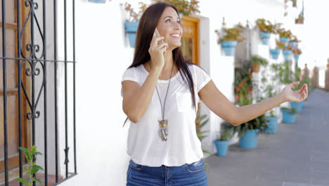 Cheerful-woman-talking-phone-at-street