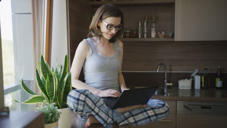 Young-woman-sitting-on-table-using-laptop