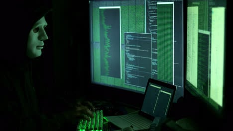 Anonymous-man-hacking-computers-in-dark-room