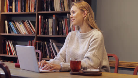 Woman-in-jumper-using-laptop-in-library