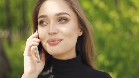 Portrait-of-beautiful-female-talking-phone-and-laughing-while-looking-away