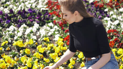 Side-view-of-female-in-casual-outfit-sitting-on-side-of-flowerbed