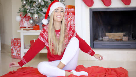 Pretty-young-woman-sitting-on-the-floor-with-christmas-tree-behind