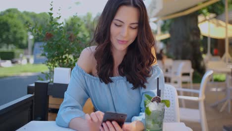 Pretty-brunette-woman-sitting-in-outdoor-restaurant-and-using-her-mobile-phone