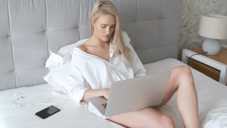 Beatutiful-woman-in-mens-elegant-white-shirt-sitting-in-bed-with