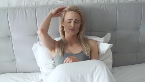 Women-sitting-on-bed-holding-her-head-She-has-a-painful-headache