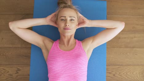Fitness-determined-middle-aged-woman-lying-doing-crunches-at-home-on-gym-mat