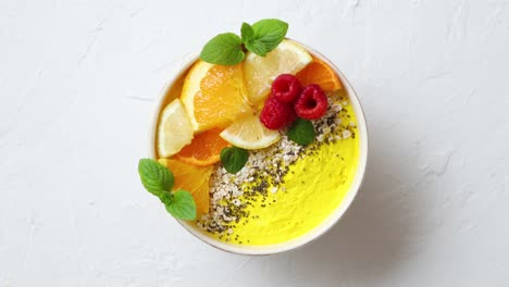 Tasty-orange-fresh-smoothie-or-yogurt-served-in-bowl-With-raspberries-orange-slices-chia-seeds