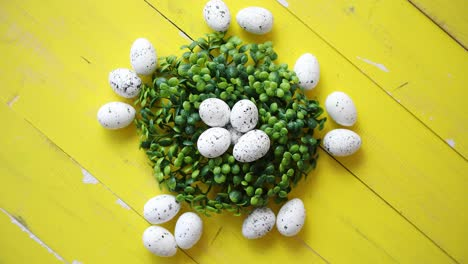 Green-decorative-Easter-quail-eggs-wreath-on-yellow-wooden-table