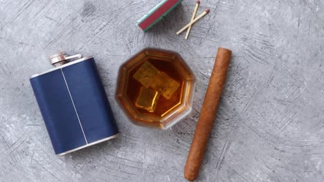 Glass-of-whiskey-with-ice-big-cuban-cigar-matches-and-hip-flask
