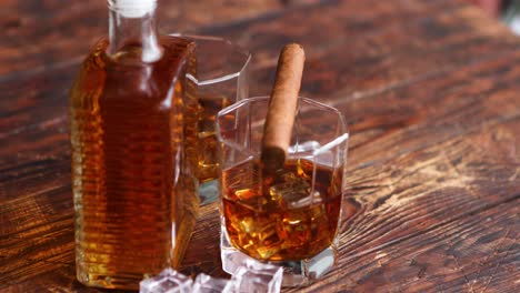 Bottle-of-whiskey-with-two-glasses-and-cuban-cigar-placed-on-rustic-wooden-table