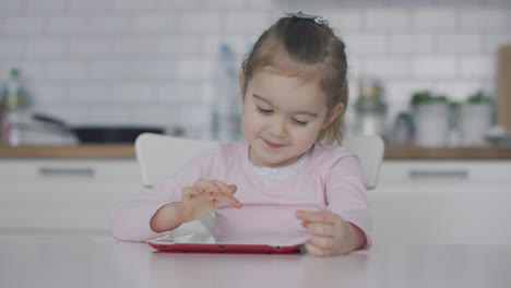 Little-girl-using-tablet-in-kitchen