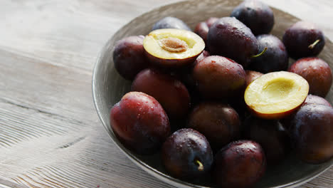 Bowl-of-fresh-plums-in-daylight