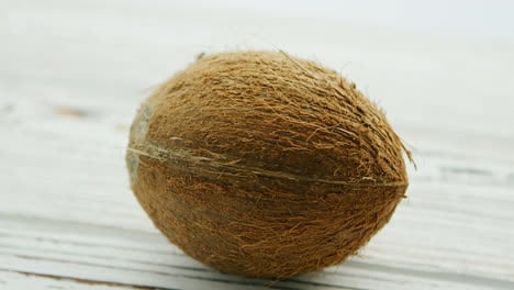Unpeeled-brown-coconut-on-table