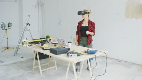 Woman-using-virtual-reality-goggles-in-workshop-