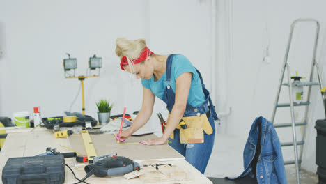 Female-carpenter-drawing-lines-on-plywood-sheet-