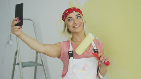 Cheerful-female-taking-selfie-with-paint-roller