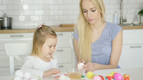Cheerful-girl-painting-eggs-with-mother