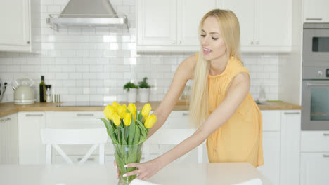 Woman-arranging-vase-with-flowers-on-table