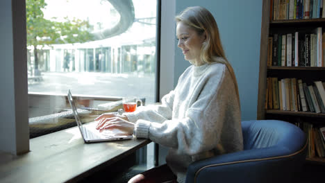 Woman-in-comfortable-armchair-using-laptop