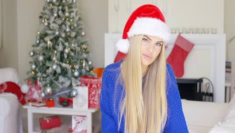 Adorable-blond-girl-in-christmas-hat-in-her-home