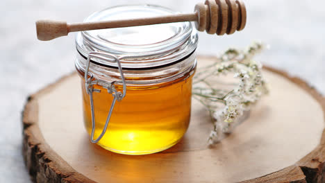 Glass-jar-full-of-fresh-honey-placed-on-slice-of-wood