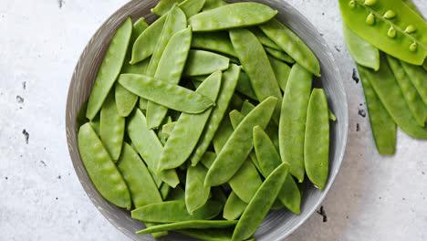 Fresh-green-peas-in-white-ceramic-bowl-on-gray-stone-background