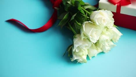Ramo-De-Rosas-Blancas-Con-En-bucle-Rojo-Sobre-Fondo-Azul-En-Caja-De-Regalo-En-El-Lateral