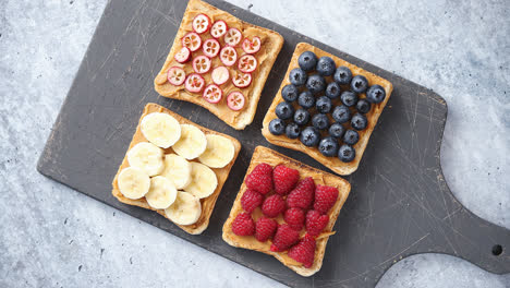 Wholegrain-bread-slices-with-peanut-butter-and-various-fruits