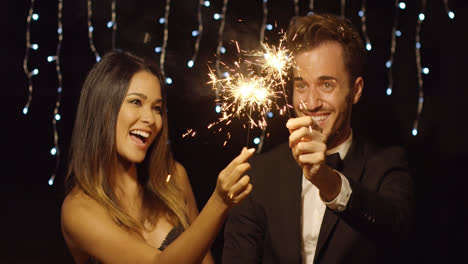 Young-couple-celebrating-new-year-with-sparklers
