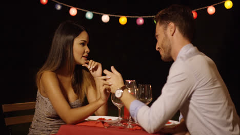 Man-gestures-at-date-across-red-covered-table