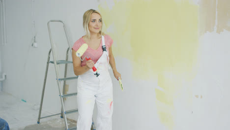 Blond-female-with-paint-roller-dancing-