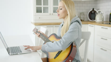 Woman-using-laptop-while-playing-guitar