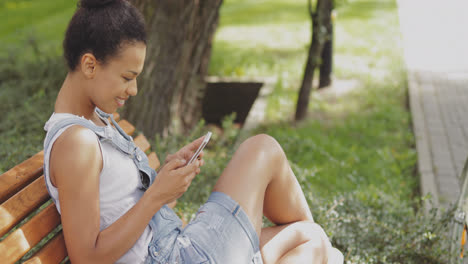 Content-girl-using-smartphone-in-park