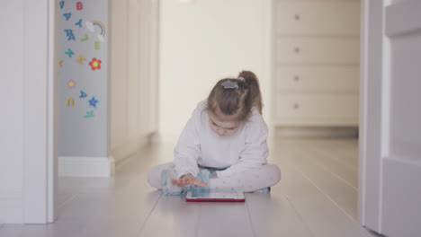 Girl-playing-tablet-on-floor-at-home