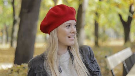 Woman-in-red-beret-sitting-on-bench