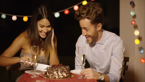 Elated-young-couple-joking-as-they-cut-the-cake