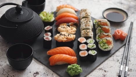 Assortment-of-different-kinds-of-sushi-rolls-placed-on-black-stone-board