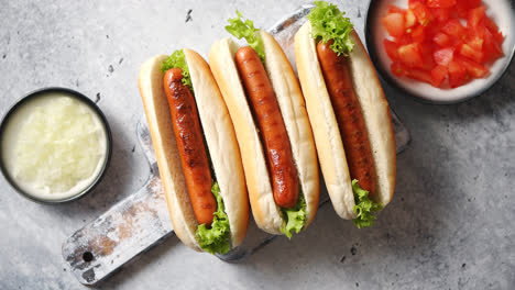 Three-barbecue-grilled-hot-dogs-with-sausage-placed-on-wooden-cutting-board