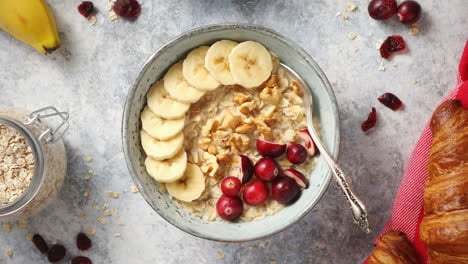 Ceramic-bowl-of-oatmeal-porridge-with-banana-fresh-cranberries-and-walnuts