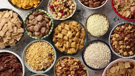 Assortment-of-different-kinds-cereals-placed-in-ceramic-bowls-on-table
