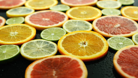 Slices-of-citruses-on-dark-table-