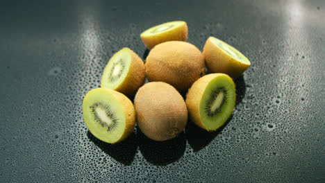 Whole-and-cut-kiwifruit-on-table-